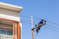Electricista que repara el alambre en polo de la energía eléctrica Fotografía de archivo libre de regalías