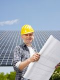 Electricista que se coloca cerca de los paneles solares Imágenes de archivo libres de regalías
