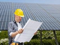 Electricista que se coloca cerca de los paneles solares Imagen de archivo libre de regalías