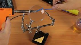 Electricista que suelda los alambres usando un soldador y una lupa almacen de video