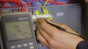 Electricista que trabaja con el disyuntor, probador, multímetro en una caja del fusible almacen de video