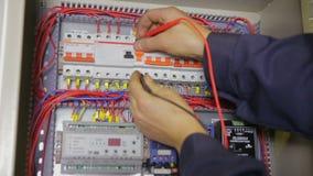 Electricista que trabaja con el disyuntor, probador, multímetro en una caja del fusible metrajes