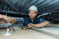 Electricista que trabaja con los alambres eléctricos en fábrica Fotografía de archivo