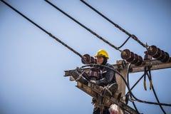 Electricista que trabaja en el polo de la electricidad Foto de archivo