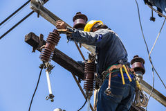 Electricista que trabaja en el polo de la electricidad Fotografía de archivo