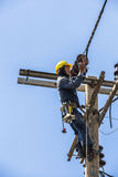 Electricista que trabaja en el polo de la electricidad Foto de archivo libre de regalías