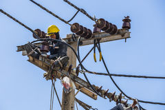 Electricista que trabaja en el polo de la electricidad Imagen de archivo
