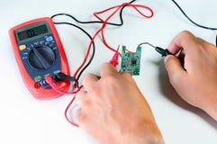 Electricista que usa el multímetro digital en taller Foto de archivo libre de regalías