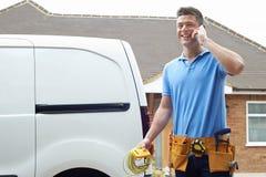 Electricista Standing Next To Van Talking On Mobile Phone imágenes de archivo libres de regalías