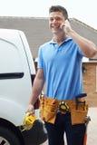 Electricista With Van Talking On Mobile Phone fuera de la casa Imagen de archivo libre de regalías