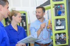 Electricistas que comprueban voltaje en zócalo eléctrico parcialmente montado fotografía de archivo libre de regalías