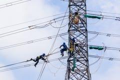 Electricistas que cuelgan líneas eléctricas de la torre Fotos de archivo