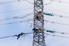 Electricistas que cuelgan líneas eléctricas de la torre Imagen de archivo