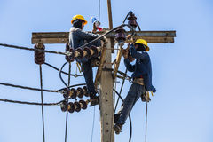 Electricistas que descansan mientras que trabaja en polo de la electricidad Imagen de archivo libre de regalías