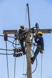 Electricistas que descansan sobre el polo de la electricidad Imagenes de archivo