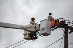 electricistas que reparan el alambre de la línea eléctrica en energía eléctrica Fotos de archivo libres de regalías