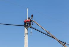 Electricistas que reparan el alambre de la línea eléctrica en polo de la energía eléctrica Fotos de archivo libres de regalías