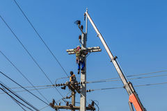 Electricistas que reparan el alambre de la línea eléctrica en polo de la energía eléctrica con la grúa Fotografía de archivo libre de regalías