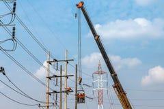 Electricistas que suben el trabajo sobre polo de la energía eléctrica con la grúa Fotos de archivo