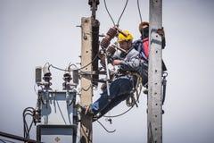 Electricistas que trabajan en el polo de la electricidad Imagenes de archivo