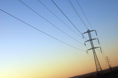 Electricity. Power supply : electrical pylons and wires on sunset background Royalty Free Stock Photo