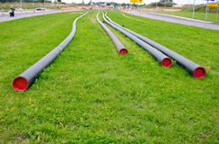 Electricity cable wire protective tube on meadow Stock Photos