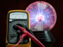 Electricity control. Digital multimeter and high voltage plasma lamp in the background royalty free stock photo