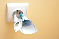 Electricity cost. Abstract with socket in the wall with euro banknotes stuck in royalty free stock images
