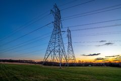 Electricity Distribution Towers and Wires at Dusk. Electricity distribution pylons and wires stand tall, silhouetted against a clear twilight sky stock photos