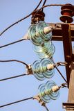 Electricity garland of insulators with electric wires on a top mast support Royalty Free Stock Image