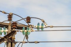Electricity garland of insulators with electric wires on a top mast support Stock Image