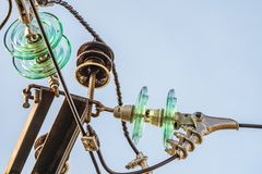 Electricity garlands of insulators with electric wires on a top steel mast support Stock Photos