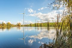 Electricity generating wind turbines reflected in the water surf. Ace of a small Dutch lake. In the foreground are reed and branches. It is a sunny day with a stock photos