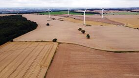 Electricity generating windmills on the green field against cloudy blue sky in England