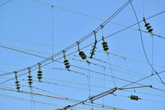 Electricity grid. Many electricity cables and condensators on a railroad against a blue sky - selective focus Royalty Free Stock Images