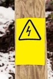 Electricity hazard plate on wood pillar Royalty Free Stock Photos