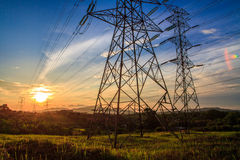 Electricity. A high voltage of transmission tower in the morning sunrise with the beauty of a blue sky Stock Image