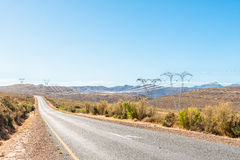 Electricity infrastructure and the road between Ceres and Touws. Electricity infrastructure next to the road between Ceres and Touws River in the Western Cape Royalty Free Stock Image