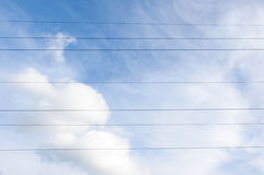 Electricity line wires against blue cloudy sky Stock Photos