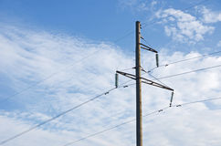 Electricity mast in front of a cloudy sky. An old power mast with wires running in front of a cloudy sky Royalty Free Stock Photo