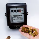 Electricity meter with the hand full of European currencies Royalty Free Stock Images