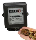 Electricity meter and the hand full of European currencies Royalty Free Stock Photography