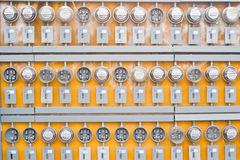 Electricity Meters. Rows above rows of electrical meters form an unusual pattern on a building's exterior wall stock photo
