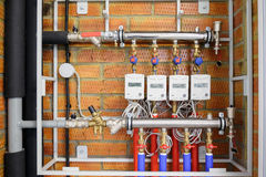 Electricity meters with pipes and wires. On a brick wall royalty free stock photos