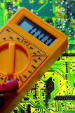 Electricity multimeter on circuit board Stock Photo