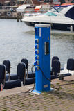 Electricity outlet in harbor. Pole with six power outlets to power private boats in small harbor Royalty Free Stock Image