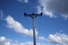 Electricity pole. Against blue sky and clouds stock photo