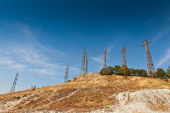Electricity pole. Electric poles on the dry grassy slope Stock Photography
