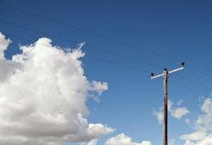Electricity Pole on Blue Sky and Fluffy Clouds Stock Photography