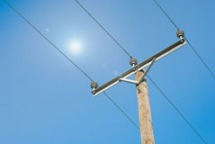 Electricity pole and cable on blue sky and sun ba Royalty Free Stock Photo